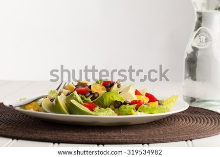 Southwest black bean, lime, cilantro, tomato, and avocado salad on a vintage antique plate side view - stock photo