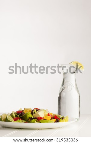 Southwest black bean, lime, cilantro, tomato, and avocado salad on a vintage antique plate vertical shot - stock photo