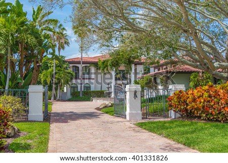 Southwest Florida Concrete Block and Stucco Home with beautiful tropical landscaping and a tile roof and fountain.  - stock photo