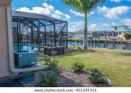 Southwest Florida homes on a canal.  View of canal homes and screened cage surrounding the pool in one of the homes along with the a/c unit sitting in the landscaping beds.  - stock photo