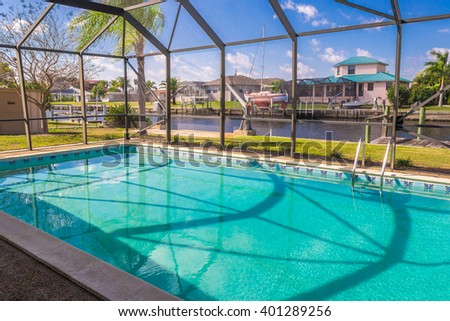 Southwest Florida homes on a canal.  View of canal homes through the screened cage surrounding the pool in one of the homes.  - stock photo