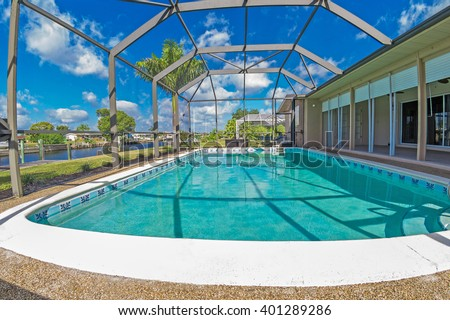 Southwest Florida homes on a canal.  View of canal homes through the screened cage surrounding the pool in one of the homes, and lanai on the right.