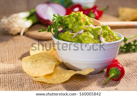 Southwest guacamole served with corn chips and pepper. - stock photo