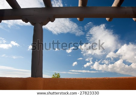 Southwestern architecture. Beams and earth colored wall against blue sky, one little tree showing up behind the wall. New Mexico - stock photo