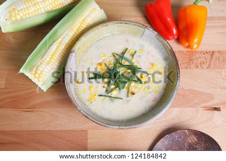 Southwestern style corn chowder soup garnished with ears of corn along with red and yellow bell peppers - stock photo