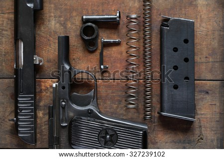 Soviet dismantled handgun on old wooden background - stock photo