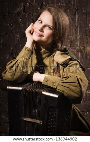 Soviet female soldier in uniform of World War II with an old accordion - stock photo
