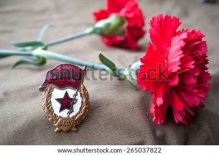 soviet guards badge and two red carnations. Still life dedicated to Victory Day. - stock photo
