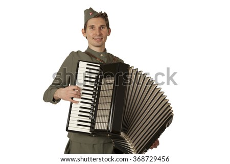 Soviet soldier in uniform of World War II playing the accordion over white background