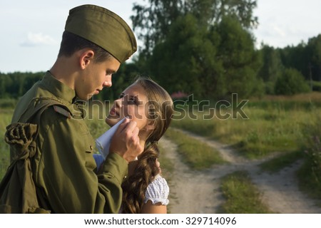 Soviet soldier in uniform of World War II saying goodbye to girl  - stock photo