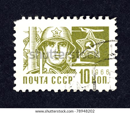 SOVIET UNION - CIRCA 1966: A stamp printed in Soviet Union showing the face of a Soviet soldier, military arsenal and the Soviet emblem, circa 1966. - stock photo