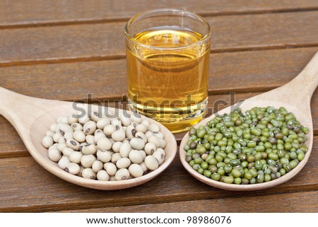 Soy beans and green beans on a teak table - stock photo