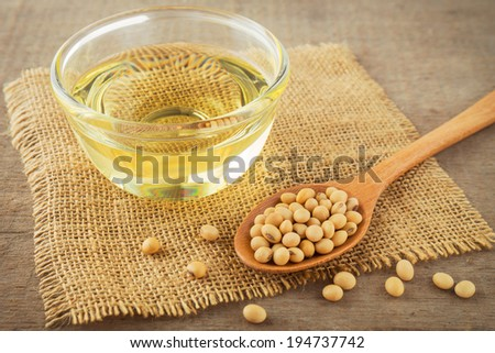 Soy beans and oil on hessian mat. - stock photo