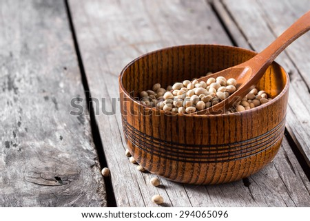 Soy beans in wooden bowl with spoon on wood background - stock photo