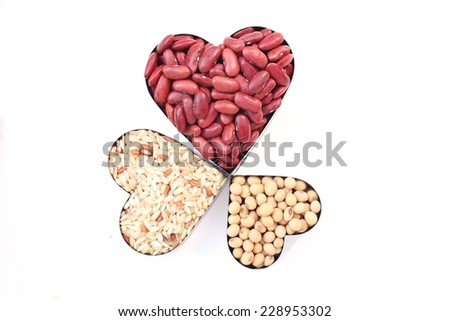 soy beans, red beans, brown rice  in heart shape are isolated on white background - stock photo