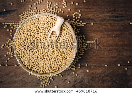 Soy beans with wooden spoon in bamboo basket - stock photo