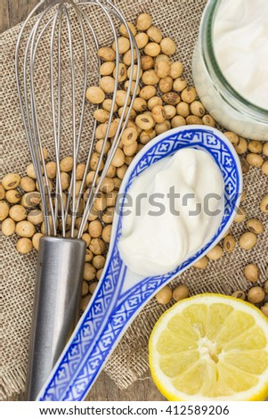 Soy mayonnaise, lemon, soybeans and metallic whip, on  cloth - stock photo