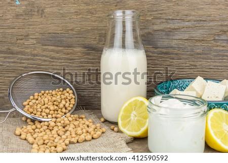 Soy mayonnaise, soy milk,tofu, lemon and soybeans, on wooden background - stock photo