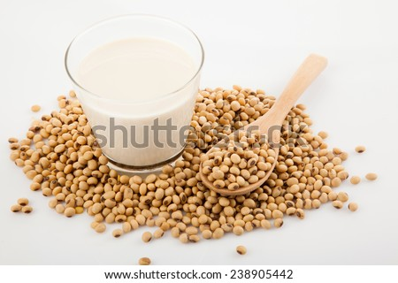 Soy milk in glass with soybeans and wooden spoon on white background - stock photo