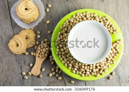 Soy milk [Soya milk ] in green cup and soy bean in wooden spoon with cookies on wooden table background. Top view. - stock photo