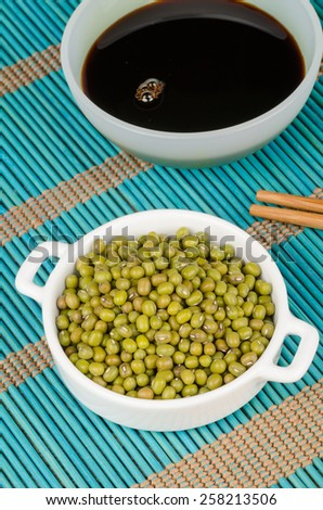 Soy sauce and soy beans on a bamboo mat - stock photo