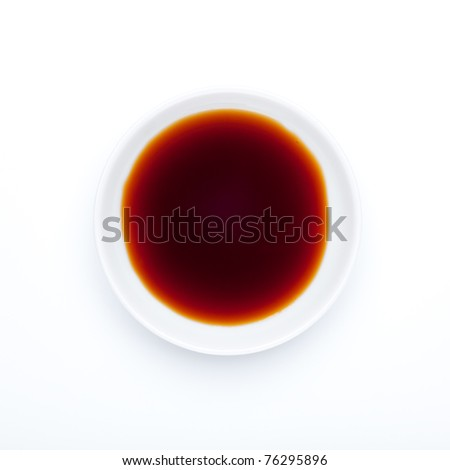 Soy sauce is a condiment produced by fermenting soybeans with a special fungus along with water and salt. Seen from directly above, on a small porcelain plate. / Spice series: Soy sauce - stock photo