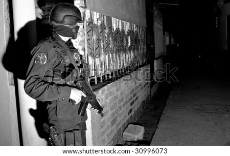 SOYAPANGO, EL SALVADOR, NOV 19: A Special Forces officer of the Grupo Reacion Policial (GRP) guards an alley during a raid against gang members on November 19, 2007 in El Salvador. - stock photo