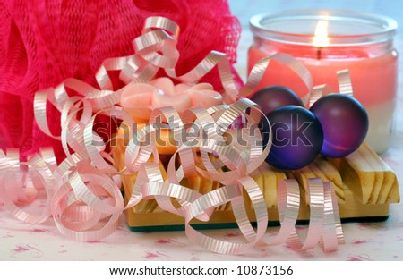 Spa accessories including bath beads, soaps, a lit candle, and ribbons.
