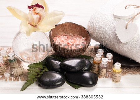 SPA accessories, stones, flowers , essential oils and mineral salt on wooden table.healthy and beauty concept - stock photo