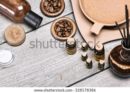 Spa and aromatherapy. Small glass vials of essential oils next to crock with incense sticks, plate with water, coffee beans, beauty product bottle, skin care cream, natural scrub on old wooden planks - stock photo
