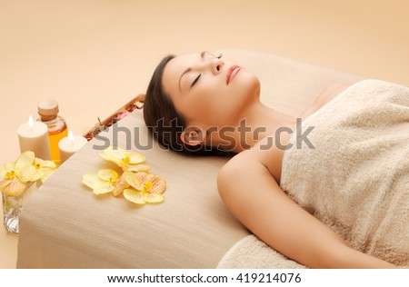 spa and beauty concept - woman in spa salon lying on the massage desk - stock photo