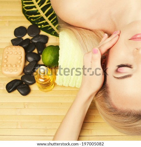 Spa and skincare concept. Portrait of beautiful girl receiving and enjoying face massage. Closed eyes. Perfect skin and make-up. Close up. Studio Shot - stock photo