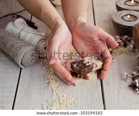Spa and wellness manicure setting with natural soap, candles and towel. Beige dayspa nature set - stock photo