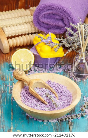Spa and wellness setting. Natural handmade lavender oil, foot massager, soap with bath salt and lavender on wooden background.  Macro, selective focus  - stock photo