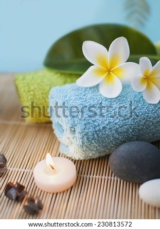 Spa and wellness setting with flowers, stones, candles and towel in blue tone - stock photo