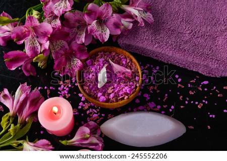 Spa and wellness setting with natural bath salt in bowl, orchid and towel - stock photo