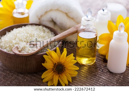 Spa and wellness setting with natural salt, aroma oils, towel. Yellow spa nature set. Selective focus. - stock photo