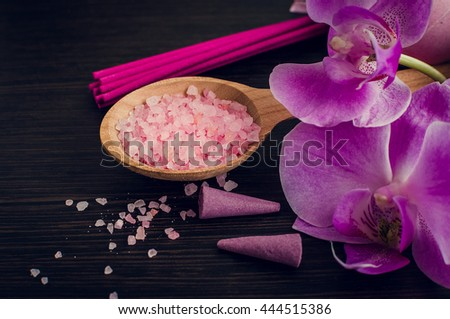 Spa and wellness still life with sea salt, orchid and aromatic incense sticks in purple, pink and violet colors on dark wooden background. Aromatherapy concept. Selective focus. - stock photo