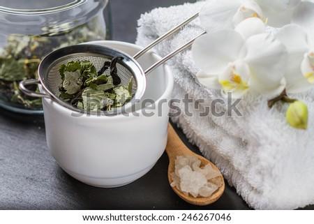 Spa and wellness - towel, orchid flowers, salt, herb tea on dark stone background - stock photo