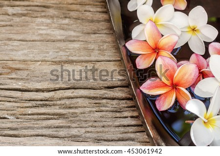 Spa & aromatherapy concept,red and white frangipani flower on wooden background. - stock photo