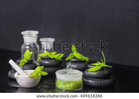 spa background of pyramid zen basalt stones with water drops, mint, sea salt, mortar, pestle and bottles of tincture on black, close up