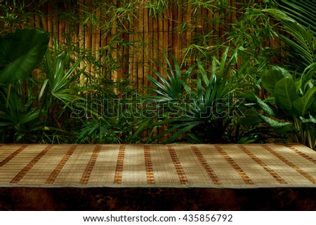 spa background. View of tropical green foliage with bamboo mat - stock photo