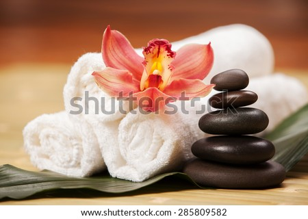Spa background. White towels on exotic plant, beautiful orchid flower and balancing stones for relax spa massage and body treatment. Asian medicine with aroma and stone therapy for beauty healthy body
