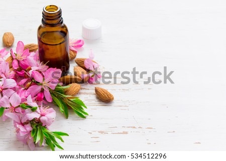 Spa background with almond essential oil and flowers.