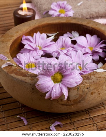 Spa background with beautiful pink blossoms in a wooden bowl. Selective focus.