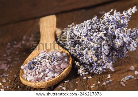 Spa background with bunch of lavender and wooden scoop with sea salt. - stock photo