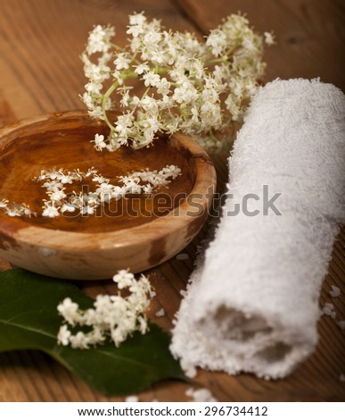 Spa background with rolled towel and bowl with water and flowers on wooden background. - stock photo