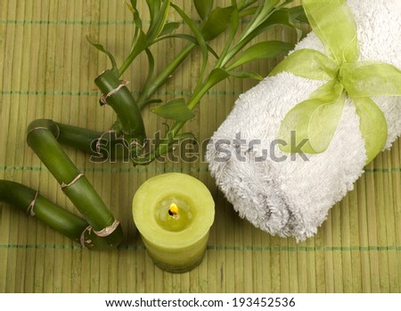 Spa background with rolled towel and green candle with bamboo on green pad. - stock photo