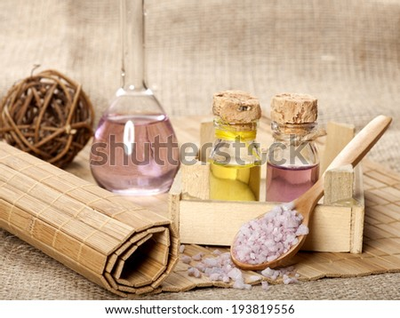 Spa background with sea salt in wooden spoon and essential oil.
