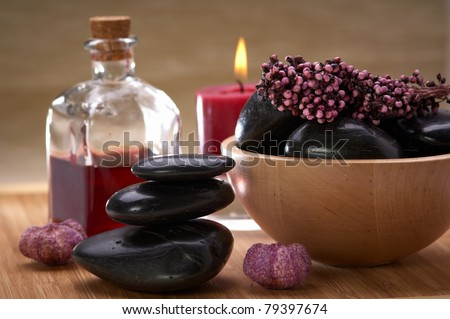 spa, balanced stones, a bowl with black stones and potpourri, bottle with essential oil and candle - stock photo